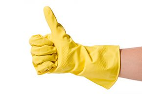 Housekeeper wearing yellow cleaning gloves, thumbs up